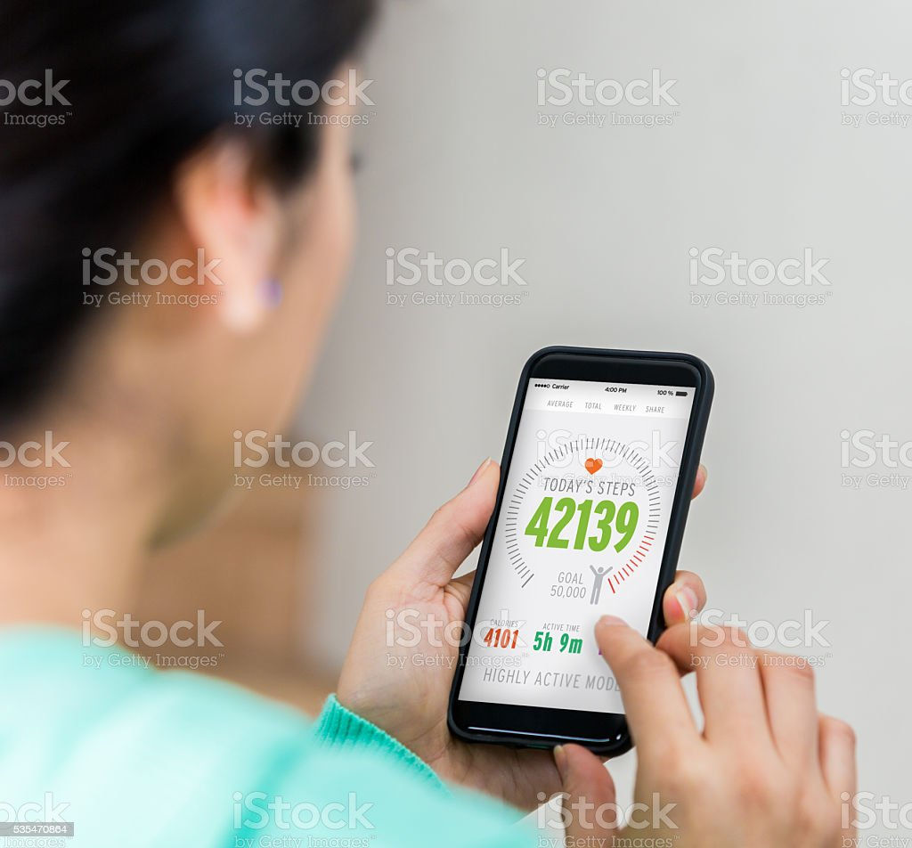 Female homeowner uses smart phone's technology to assess home security stock photo