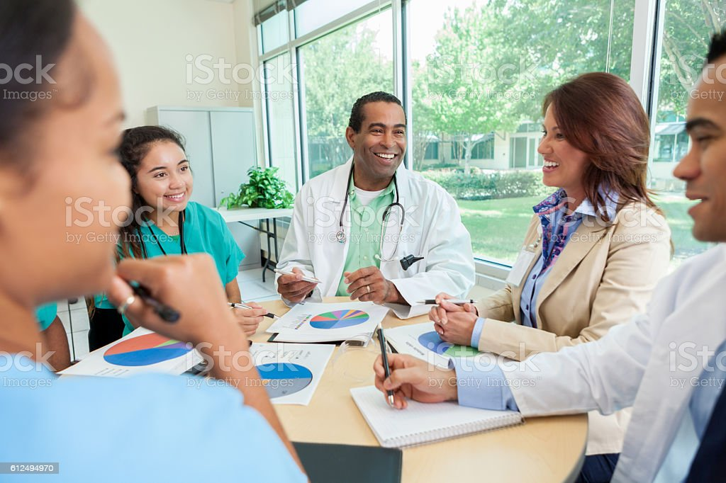 Female hospital administrator meets with hospital staff stock photo