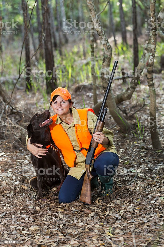 Female hunter in woods with labrador retriever stock photo