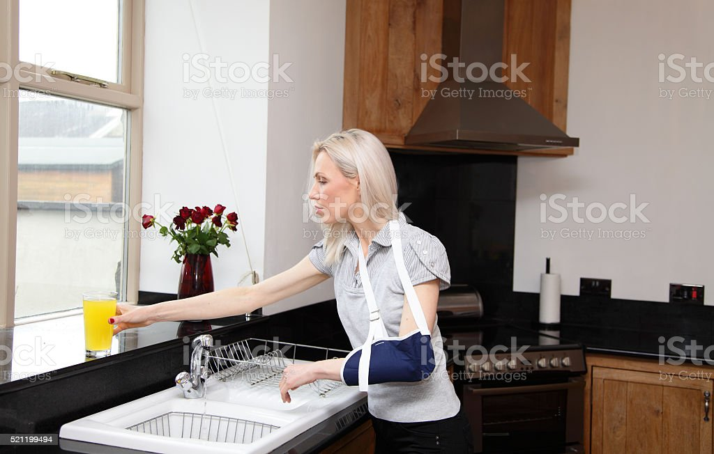 female in arm sling in kitchen stock photo