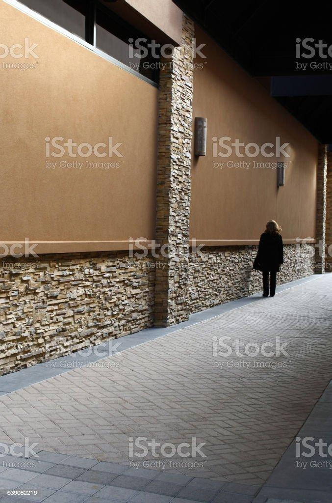 Female in dark trench coat in long corridor stock photo