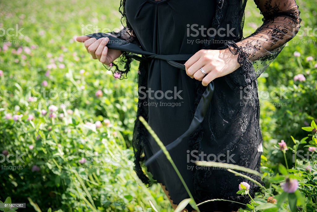Female in Lace Black Dress Outdoors stock photo