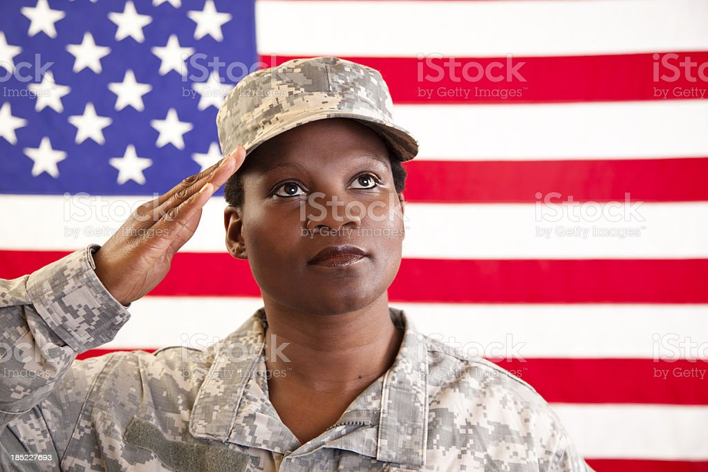 Female in military uniform saluting American flag royalty-free stock photo