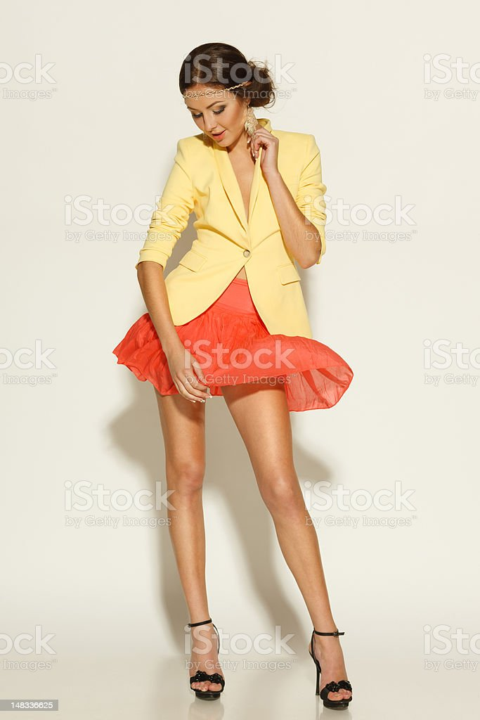 Female in mini skirt and yellow jacket stock photo