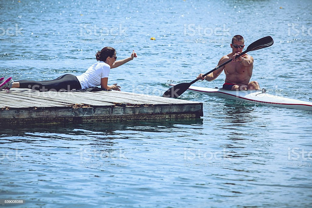 Female instructor coaching young male athlete during kayak sprint training stock photo