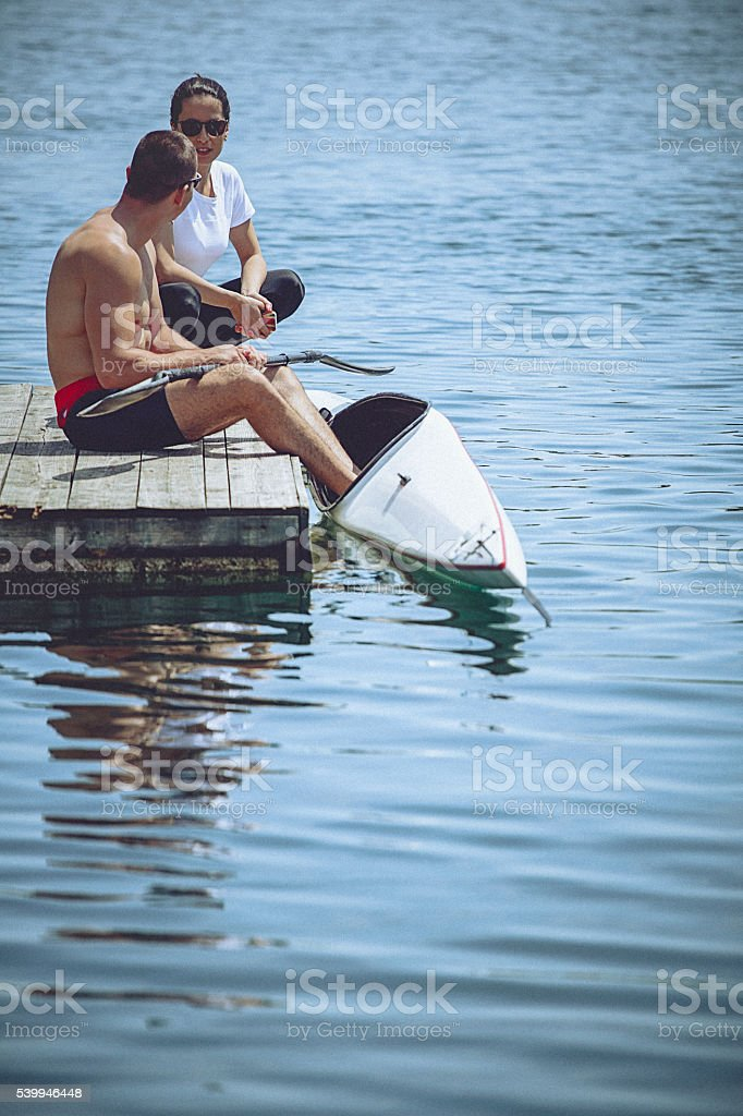 Female instructor coaching young male athlete prior kayak sprint training stock photo