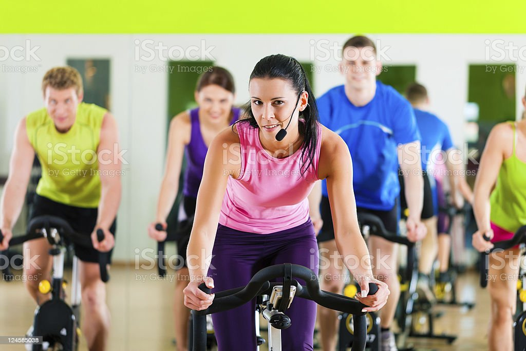 Female instructor leading an indoor gym spin class royalty-free stock photo