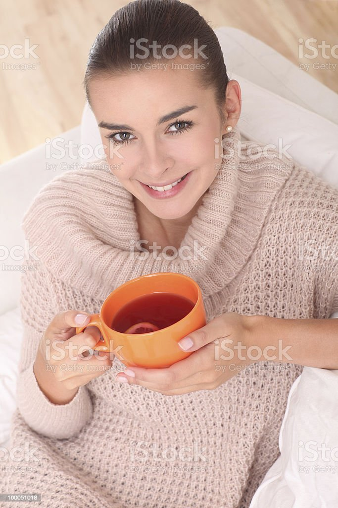 Female is drinking a tea in an orange cup. royalty-free stock photo
