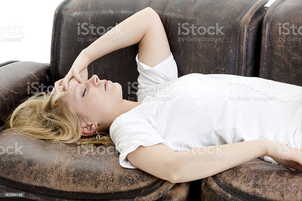 A female is laying on brown leather couch with a headache stock photo