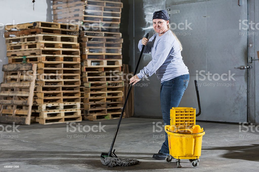 Female janitor mopping floor in warehouse stock photo