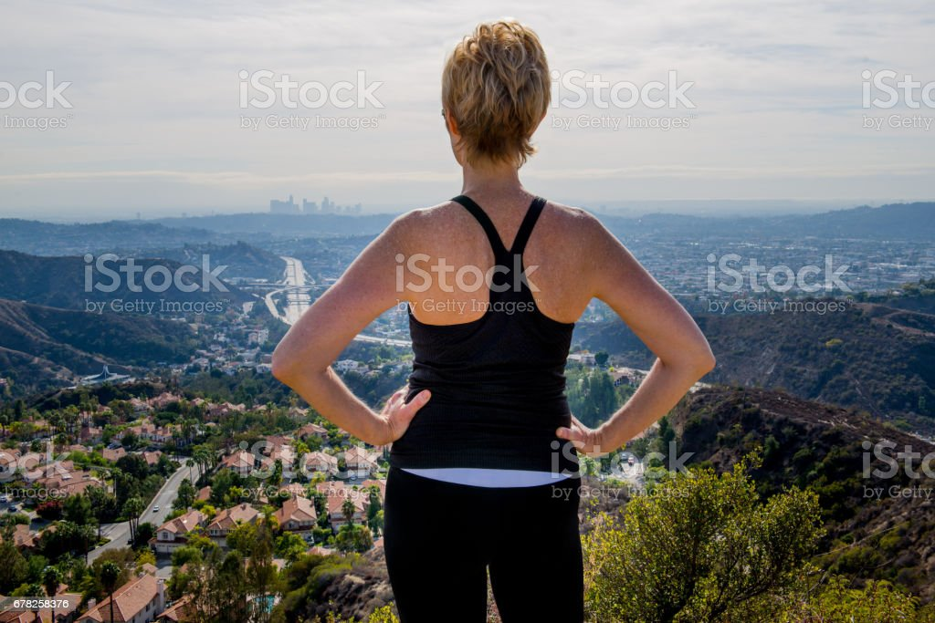 Female Jogger High on the Hill Overlooking L.A. stock photo