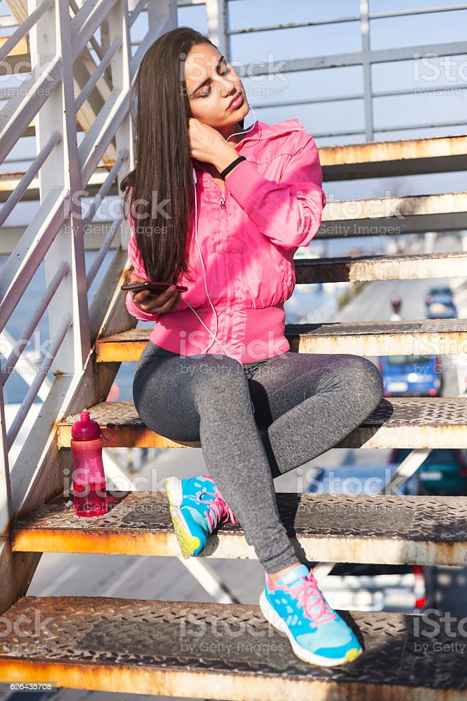 Female Jogger Using Phone and sitting on metal stairs royalty-free stock photo