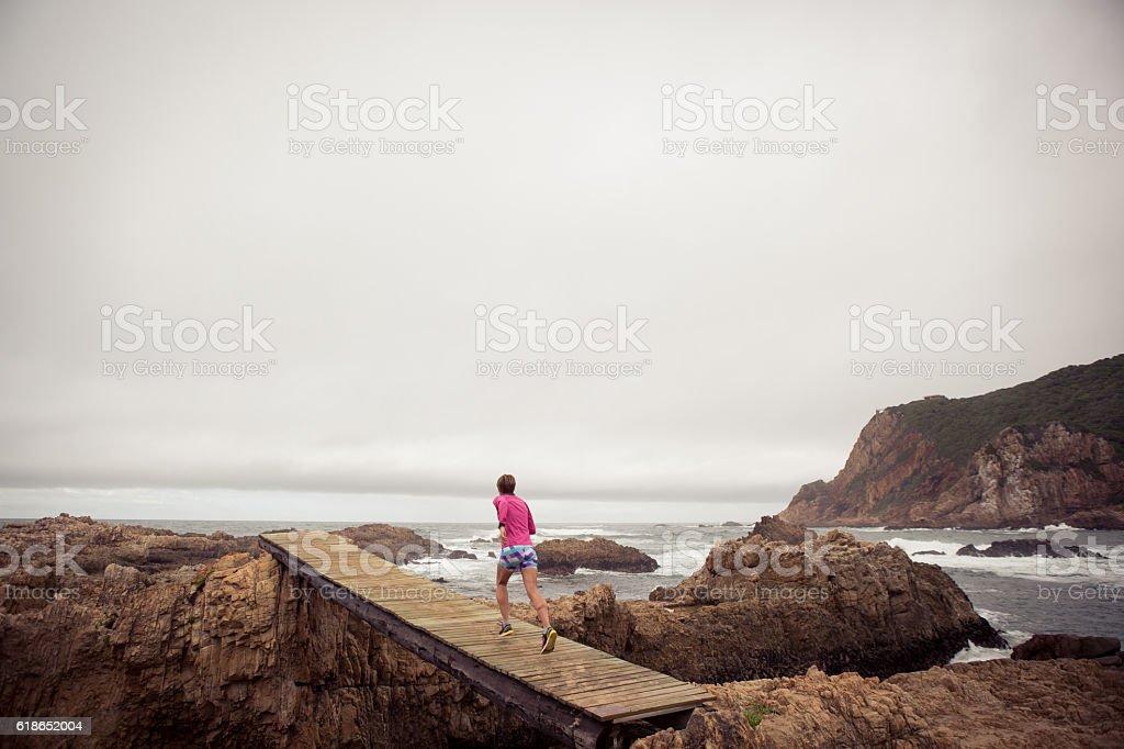 Female jogging on a wodden boardwalk near the sea stock photo