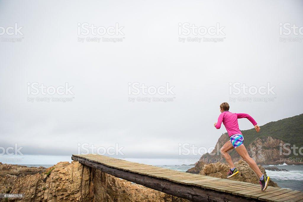 Female jogging over a wodden boardwalk near the sea stock photo