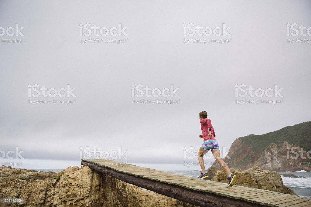 Female jogging over a wodden boardwalk near the sea stock photo