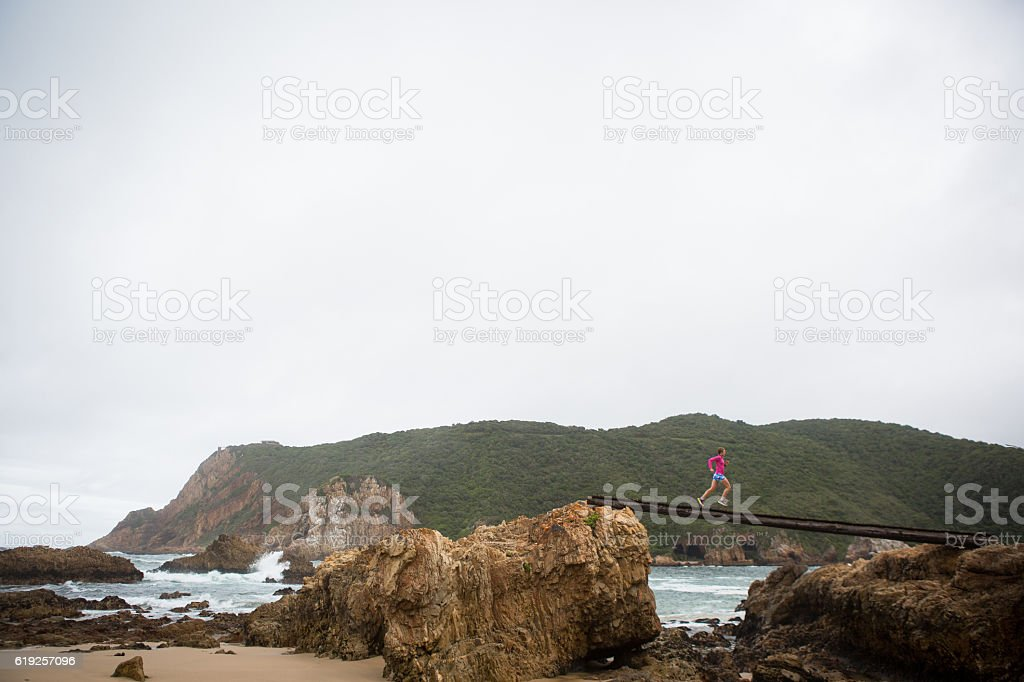Female jogging over an elevated boardwalk stock photo
