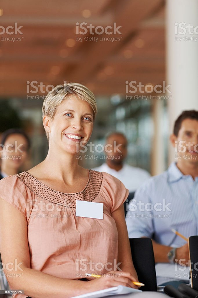 Female journalist sitting in a meeting with colleagues royalty-free stock photo