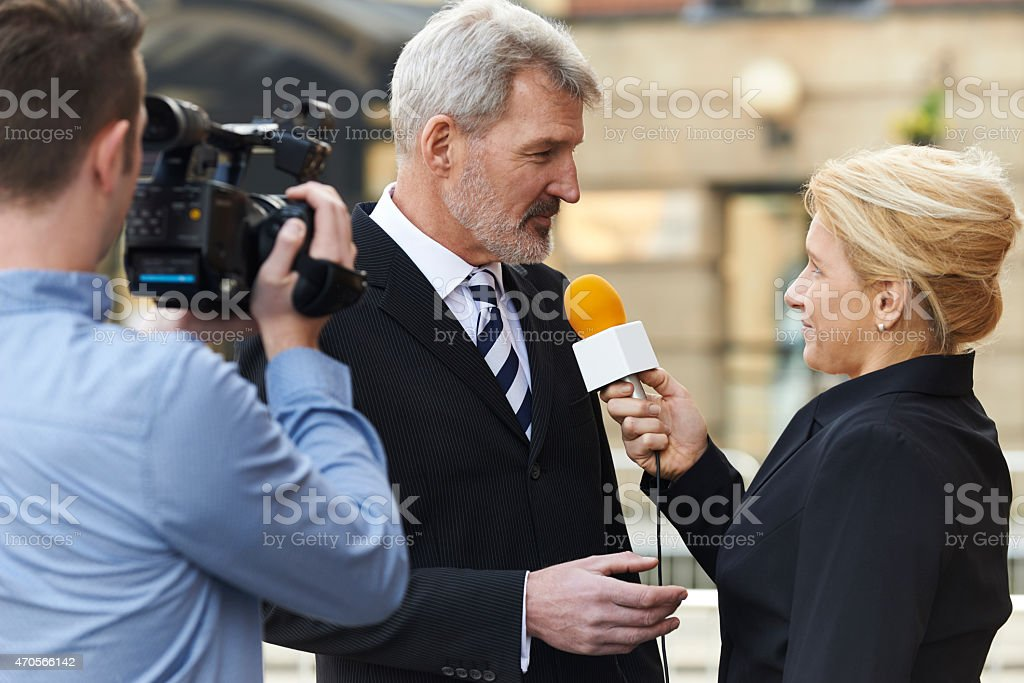 Female Journalist With Microphone Interviewing Businessman stock photo