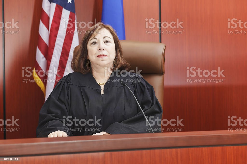 Female Judge Seated in Courtroom stock photo