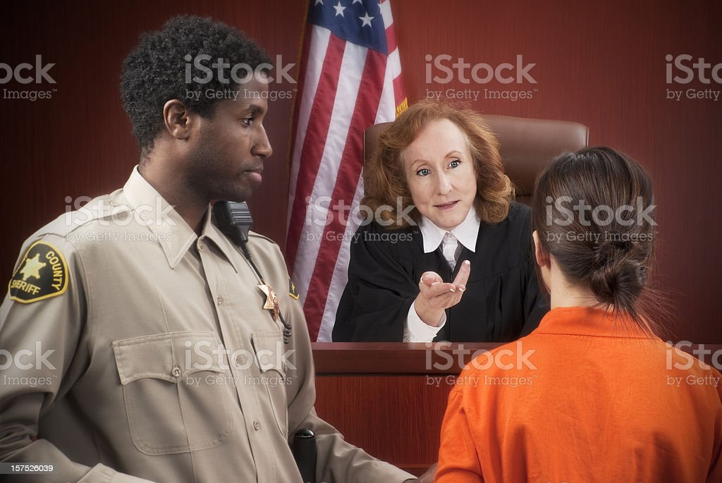 Female judge talking to a prisoner with court officer watching stock photo