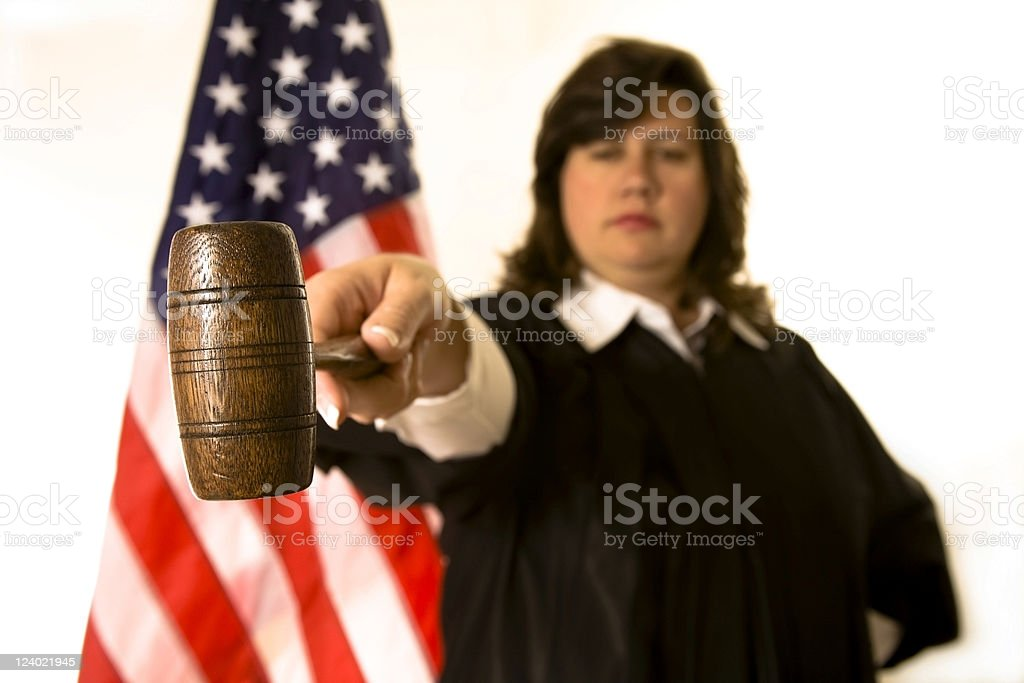 Female judge wearing black robe pointing with gavel. royalty-free stock photo