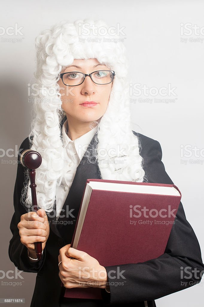 Female judge wearing  wig and Back mantle  holding judge gavel and book stock photo