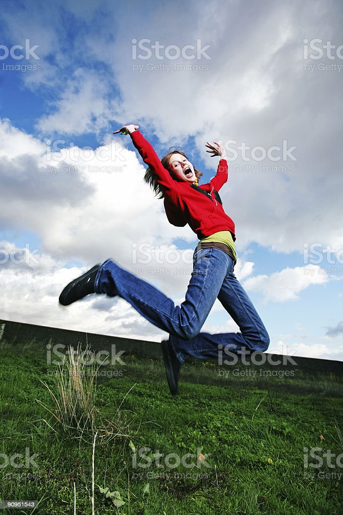 Female Jumping in Field with Excitement Portrait royalty-free stock photo