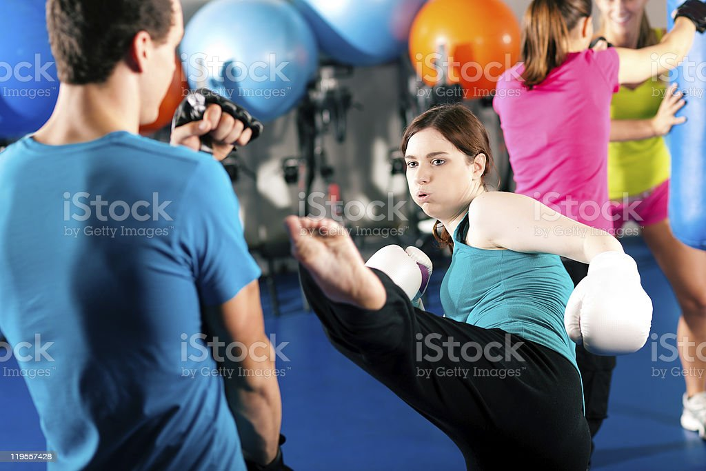 Female kick boxer sparring with trainer stock photo