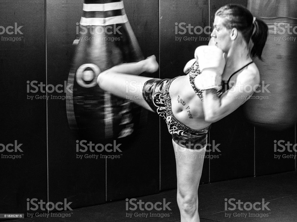 Female kickboxer working-out on bag stock photo