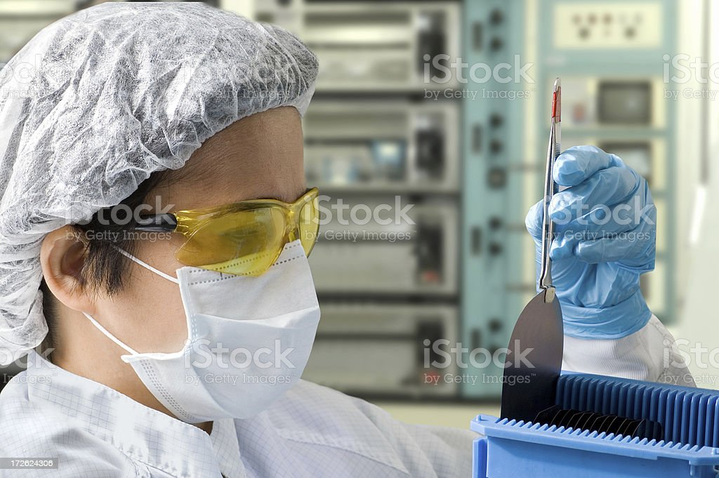 Female Lab Technician Inspecting A Silicon Wafer stock photo