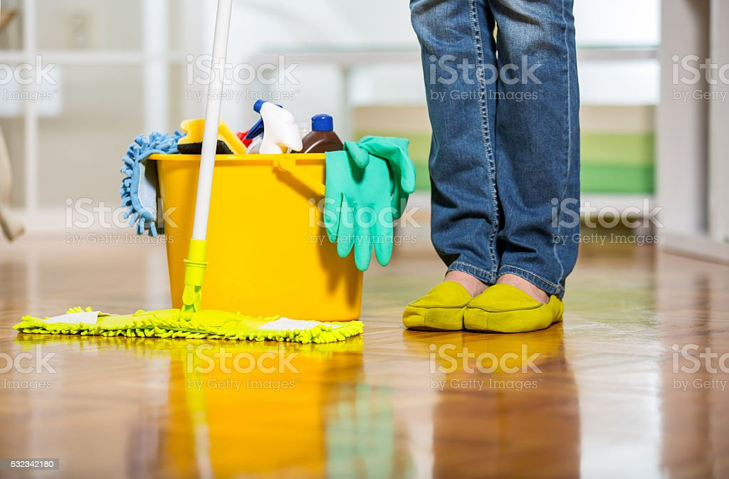 Female legs beside bucket with cleanser. stock photo