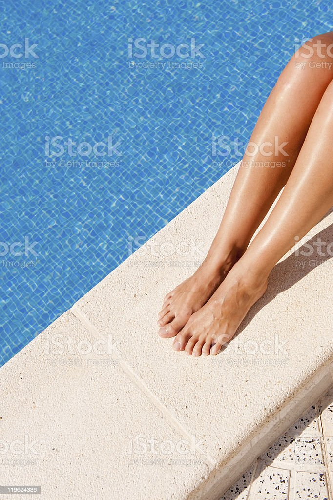 Female legs by the pool stock photo
