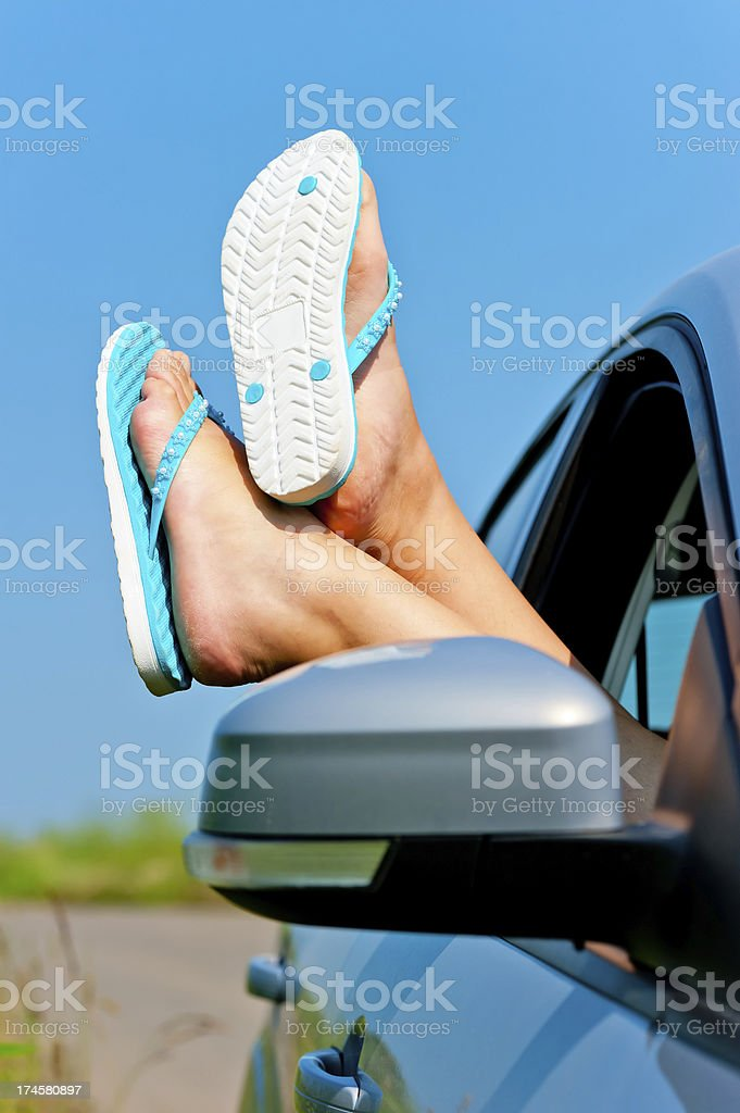 female legs dangling from the open car window in shales royalty-free stock photo