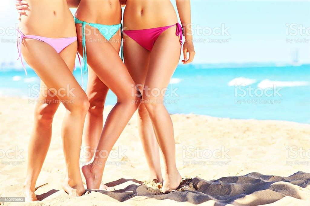 Female legs in bikini on the beach stock photo