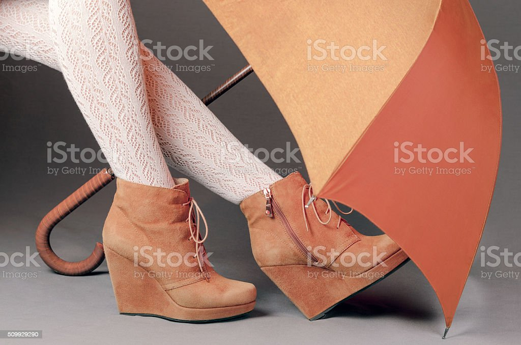 Female legs in brown suede boots under an umbrella stock photo