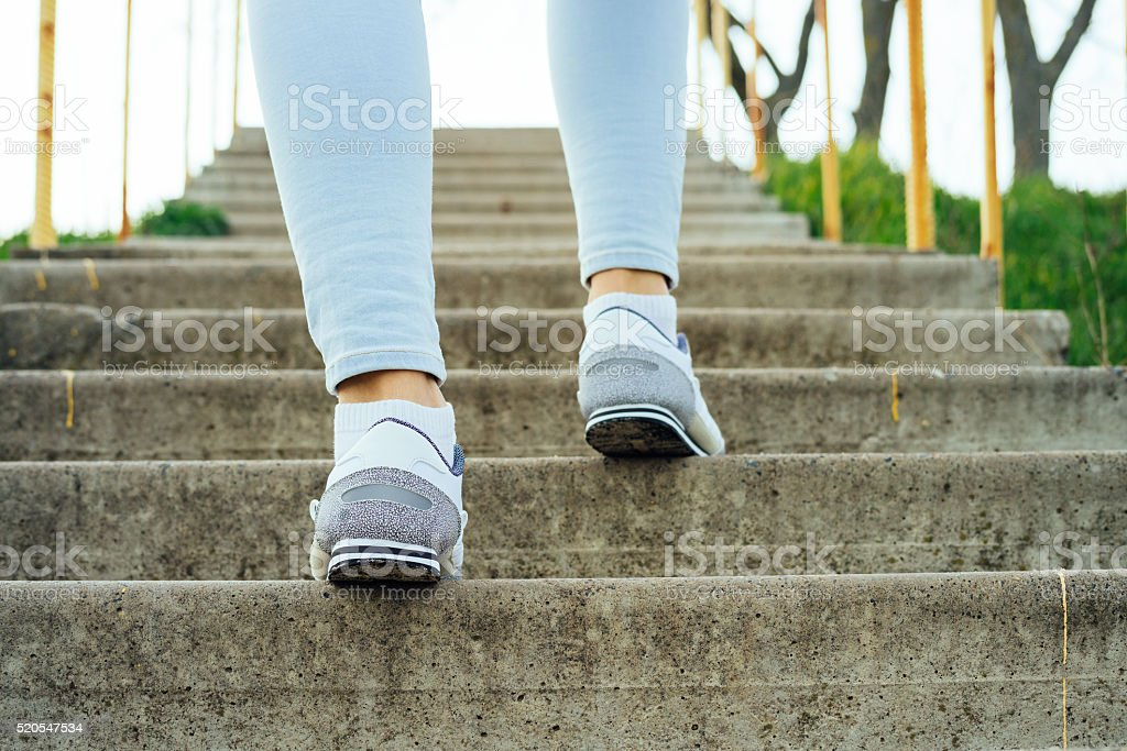 Female legs in jeans and sneakers, climb the concrete stairs stock photo