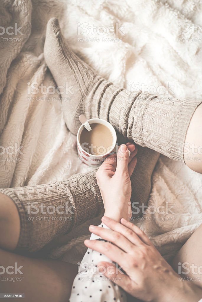 Female legs in knitted socks with cup of  coffee stock photo