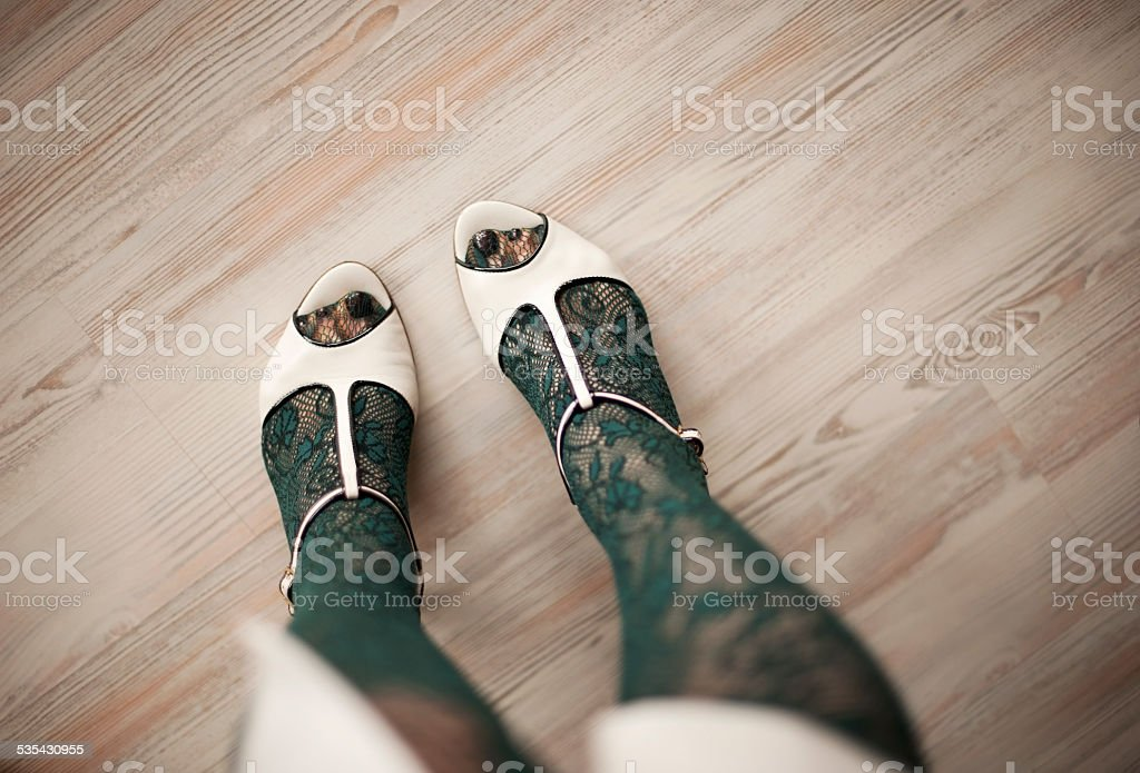 Female Legs in Lace Green Pantyhose and White Sandals stock photo