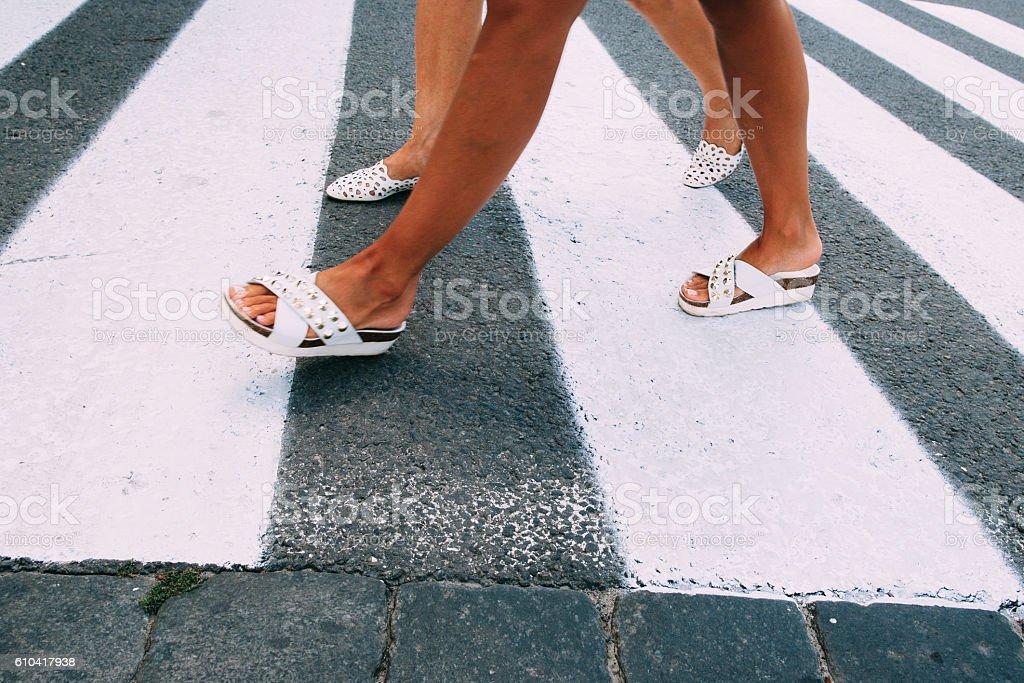 Female legs in white shoes going on zebra stock photo