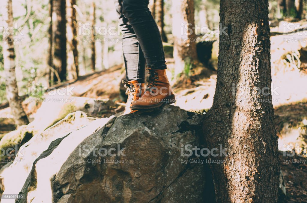 Female legs shod in Hiking boots on the forest background. Travel concept stock photo