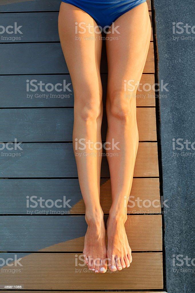 Female legs sunbathing. Depilation , waxing, cellulite free. stock photo