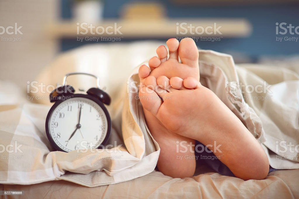 female legs under the blanket and alarm clock stock photo