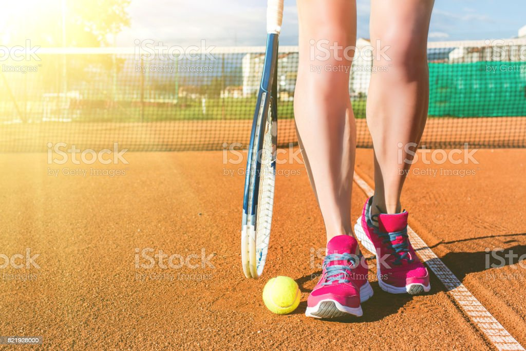 Female legs with tennis racket stock photo