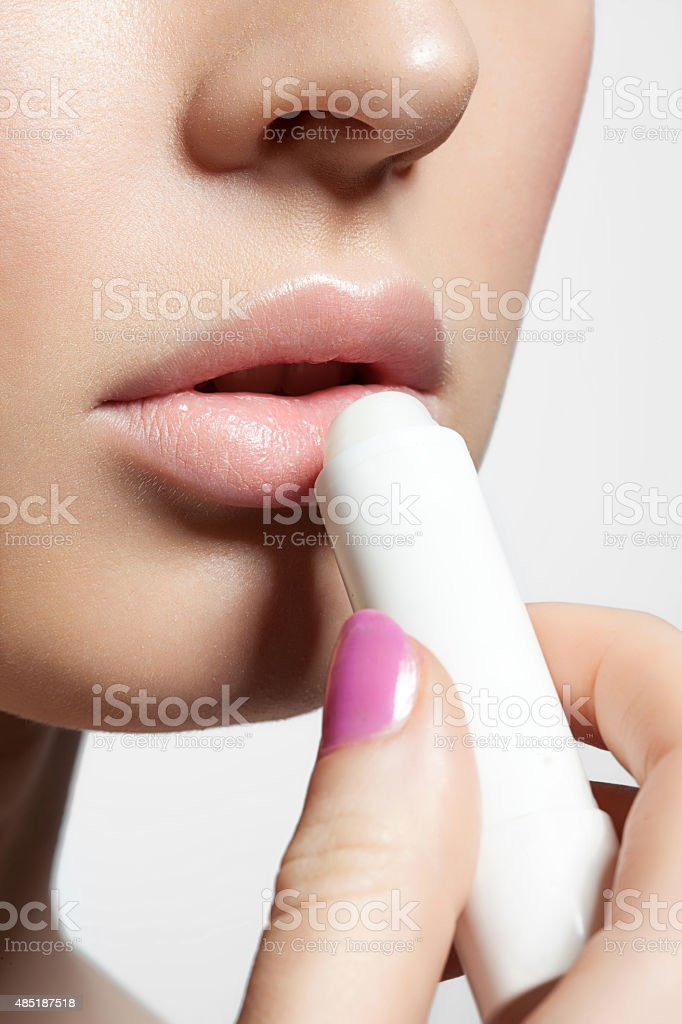 Female lips with a protective balm stock photo