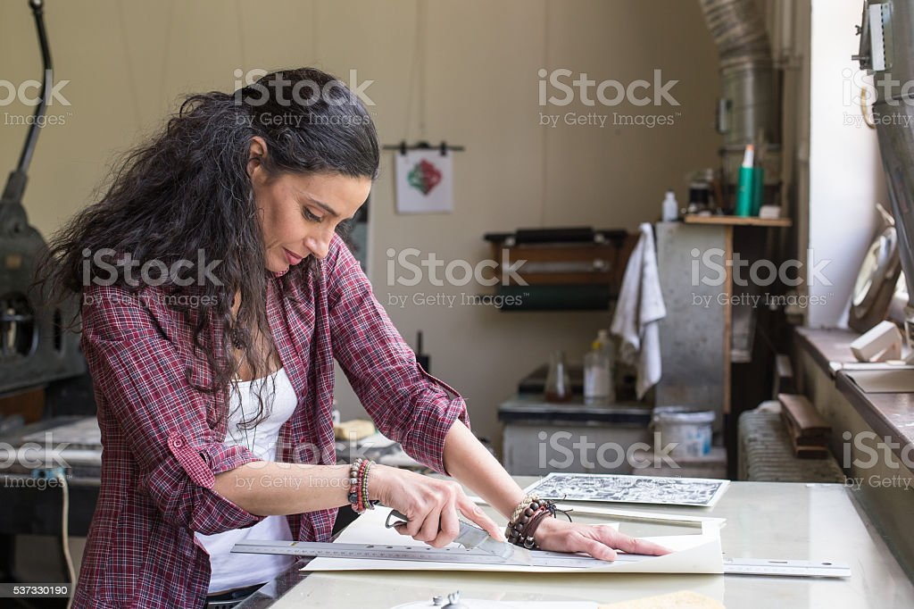 Female lithograph worker using cutter knife at workshop stock photo