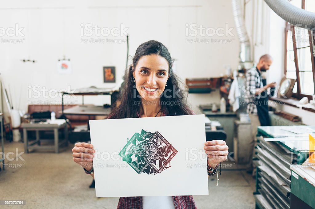 Female lithography worker holding paper with new artifact stock photo