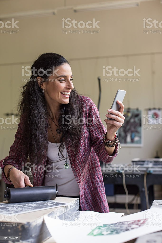 Female lithography worker making selfie at workshop stock photo