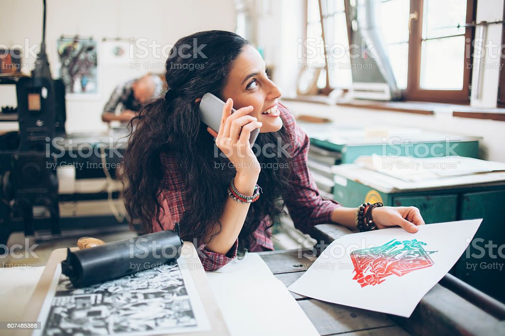 Female lithography worker using phone at printing house stock photo