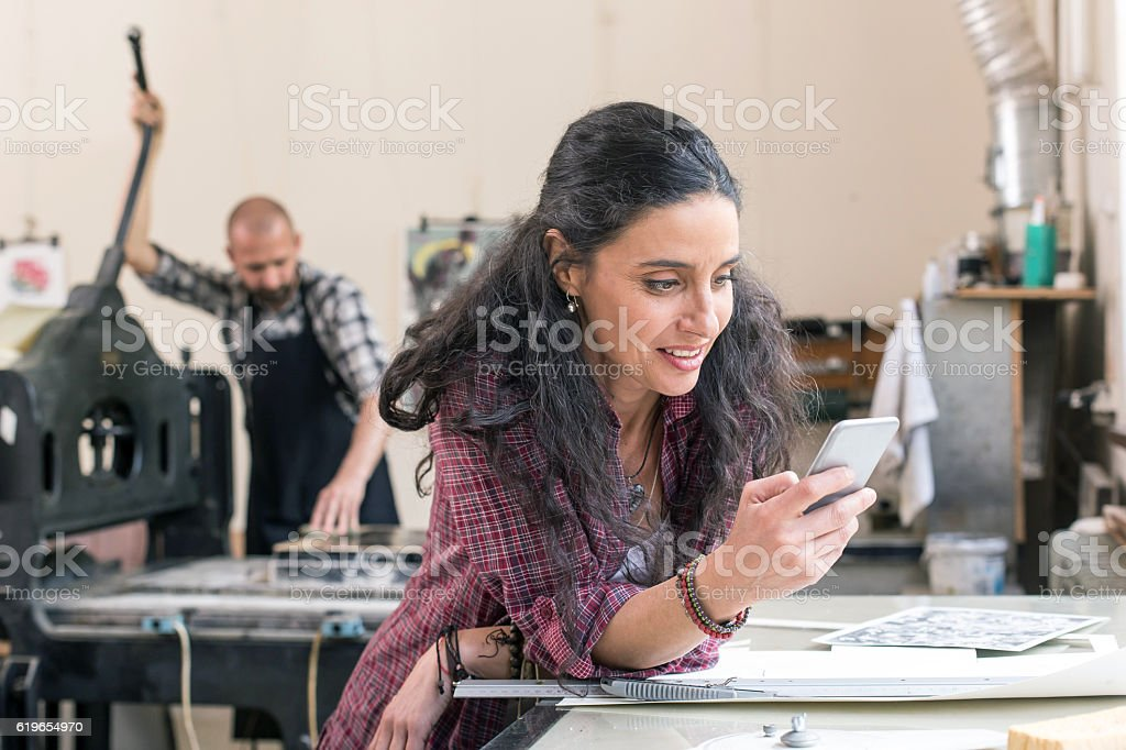 Female lithography worker using smart phone at workshop stock photo