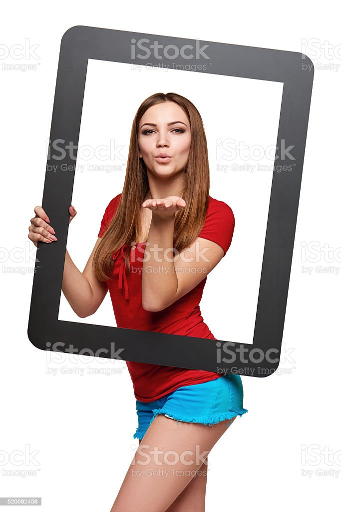 Female looking through the frame blowing a kiss stock photo